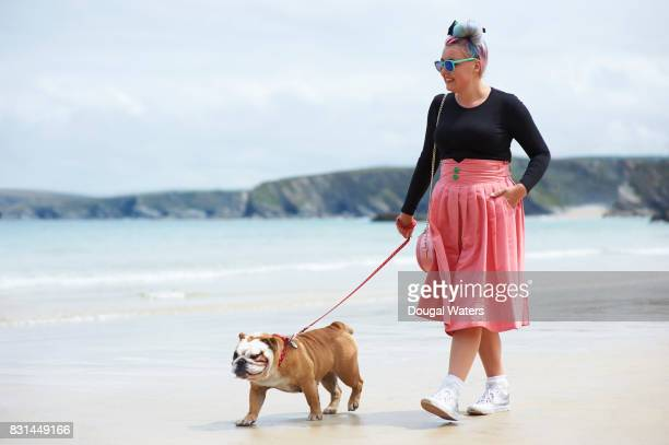 Woman walking English Bulldog at beach.