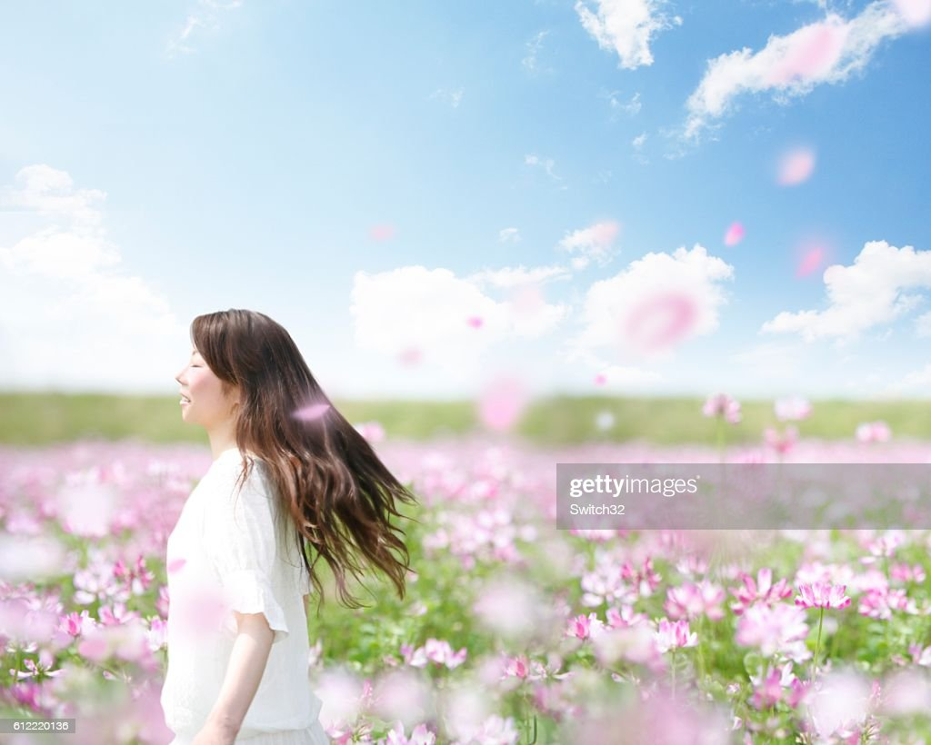 A Woman Walking Happily Through A Field Of Pink Flowers And Floating