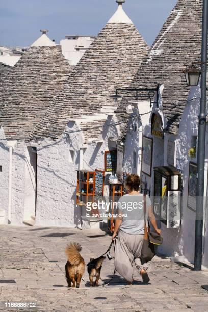Woman walking her dog in Alberobello, Italy