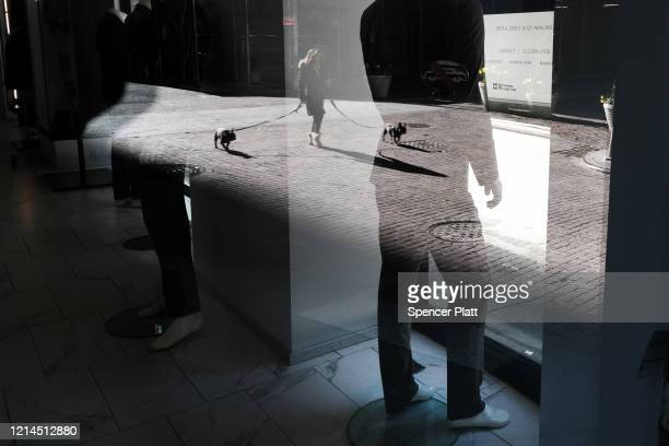 Woman walking her dogs is reflected in the window of a store near Wall Street as people stay away from the area due to the coronavirus on March 24,...