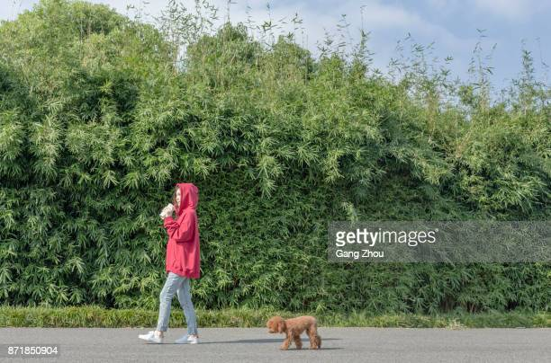 woman walking her poodle in park