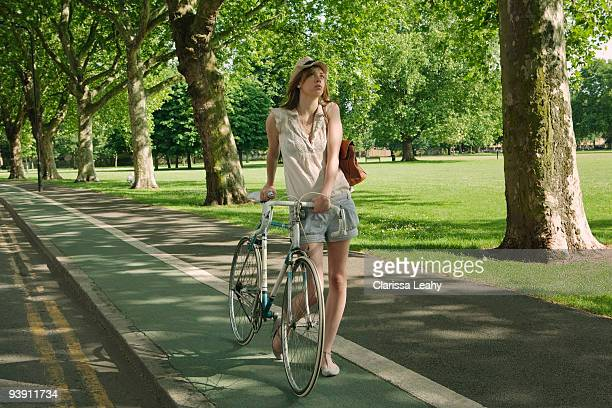Woman walking holding bike