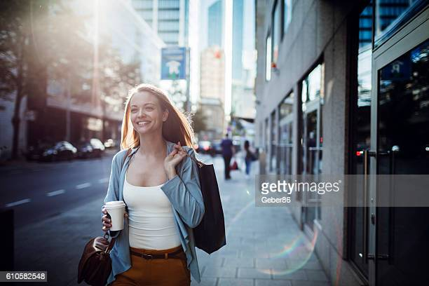 woman walking home after shopping - unterwegs stock-fotos und bilder