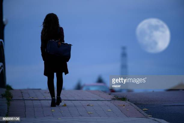 woman walking home on dark bridge - danger stock photos and pictures
