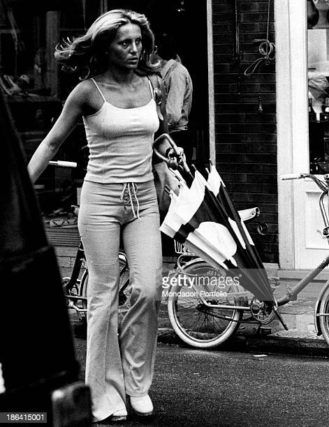 A woman walking hurriedly along the street with a closed umbrella in her left hand she wears lightcoloured laced pants and a a tight short singlet...