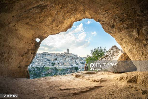 woman walking in a cave of matera, basilicata, italy - matera italy stock pictures, royalty-free photos & images