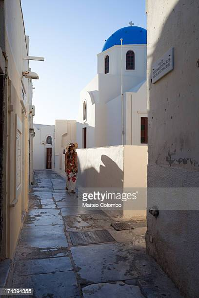 Woman walking in a narrow street, Oia, Greece