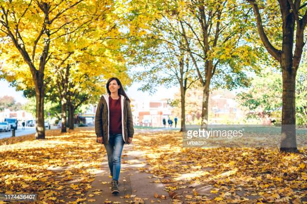 woman walking in a park - natural parkland stock pictures, royalty-free photos & images