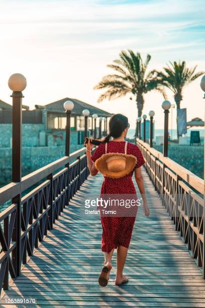 woman walking in a seaside tropical resort on summer vacation - tourism stock pictures, royalty-free photos & images