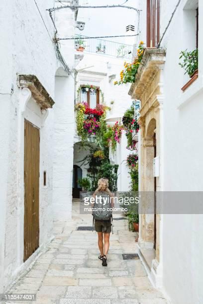 woman walking in alley in the city of alberobello, puglia, italy - alberobello foto e immagini stock
