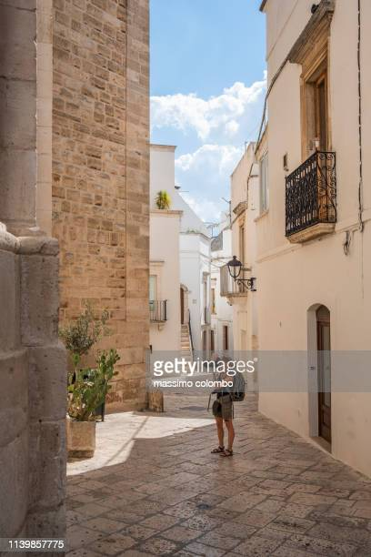 woman walking in alley in the city of alberobello, puglia, italy - ブリンディシ ストックフォトと画像