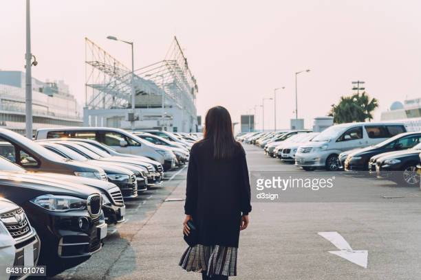 Woman walking in an outdoor car park