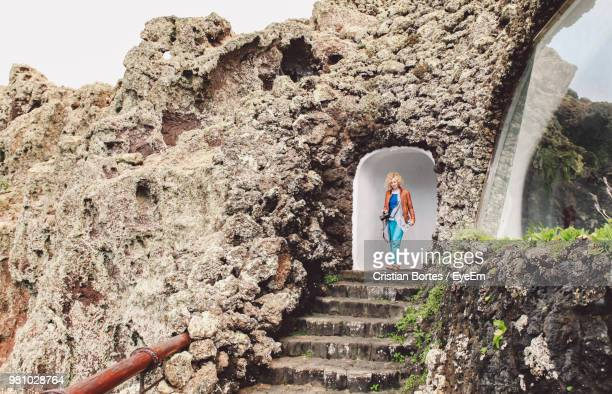 Woman Walking In Archway Of Old Ruin