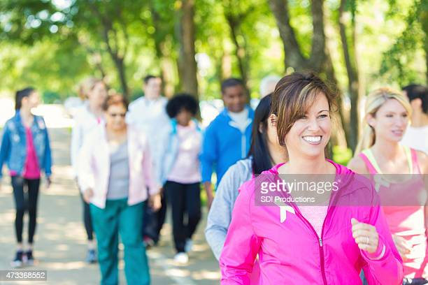 woman walking in breast cancer awareness charity race event - charity benefit stock pictures, royalty-free photos & images