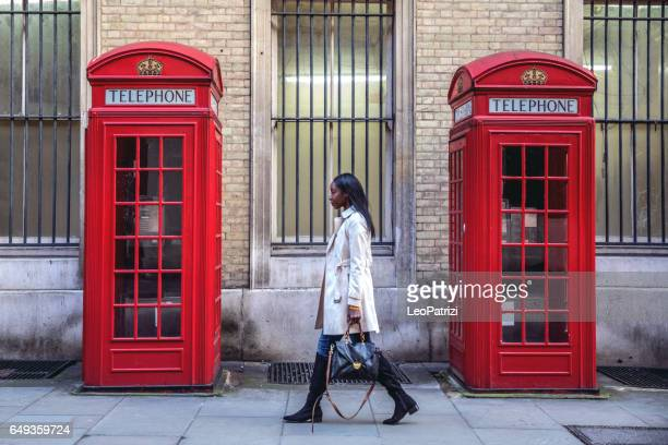woman walking in central london for shopping - telephone booth stock pictures, royalty-free photos & images