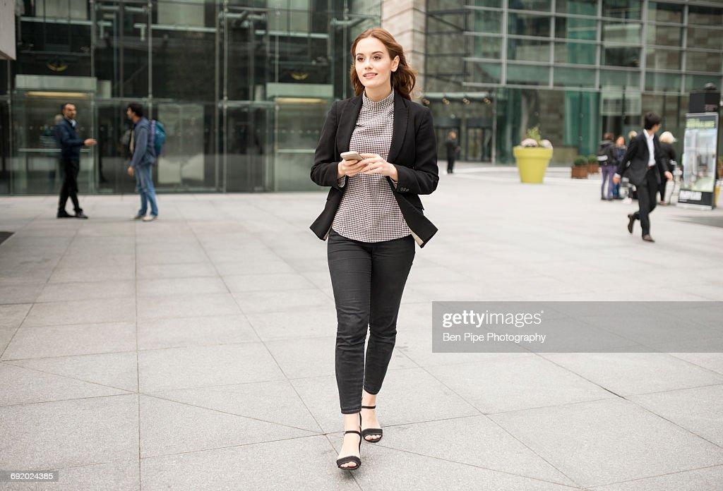 Woman walking in city holding smartphone : Foto de stock
