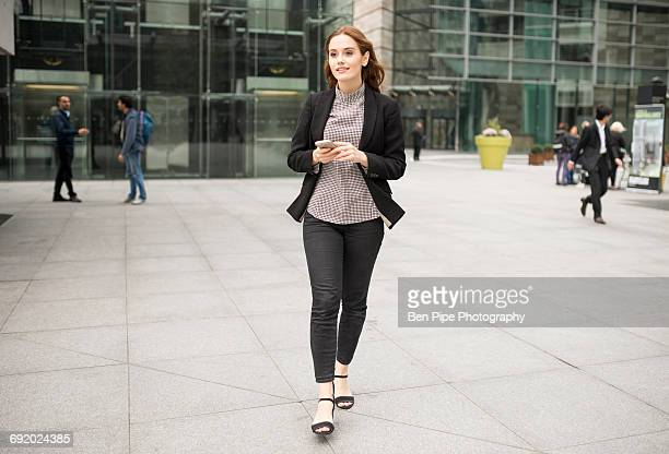 woman walking in city holding smartphone - marcher photos et images de collection