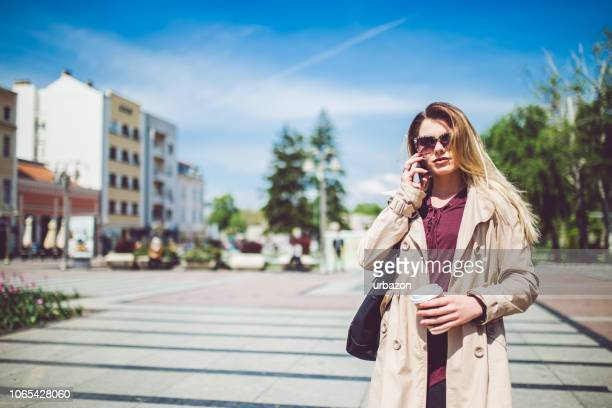 woman walking in city square and using mobile phone. - frock coat stock pictures, royalty-free photos & images