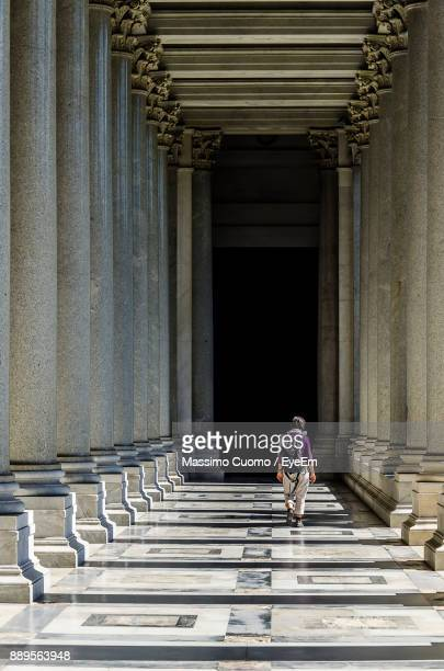 woman walking in corridor of building - cuomo stock pictures, royalty-free photos & images