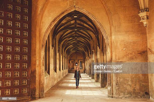 woman walking in corridor of church - cambridge stock pictures, royalty-free photos & images