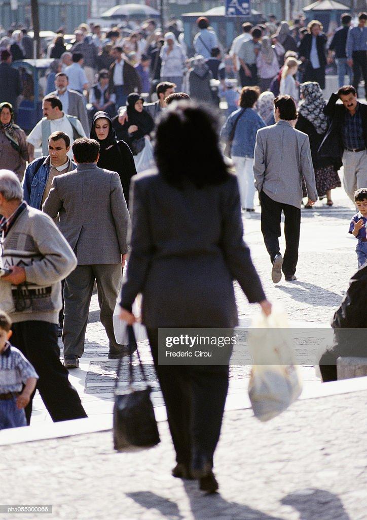 Woman walking in crowded street, rear view, blurred : Stockfoto
