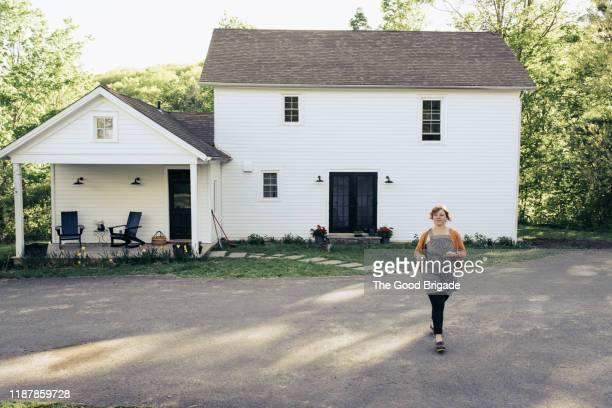 Woman walking in driveway outside house