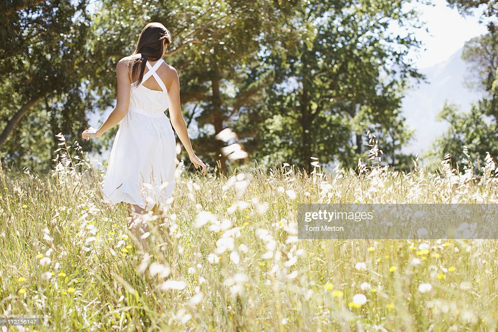 Woman walking in field : Stock Photo