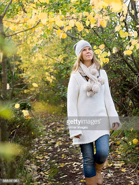 woman walking in forest - mid adult woman sweater stock pictures, royalty-free photos & images