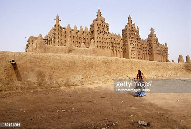 A woman walking in front of Grand Mosque of DjenneMali