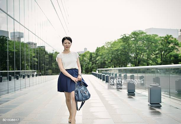 woman walking in front of office building - japanese short skirts stock photos and pictures