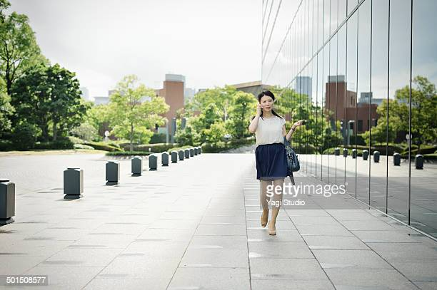 Woman walking in front of office building