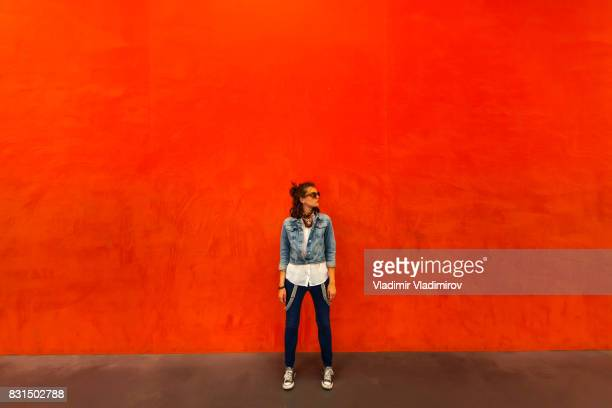 Woman walking in front of red background