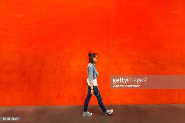 赤の背景の前に歩いている女性