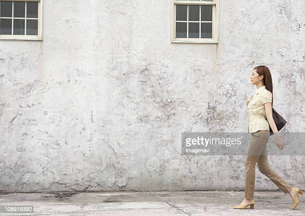 woman walking in front of wall - blouse ストックフォトと画像