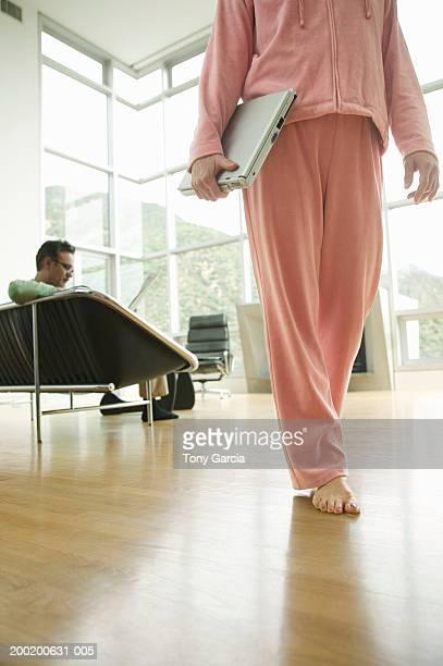 woman walking in house with laptop, man reading paper in background - trainingsanzug stock-fotos und bilder