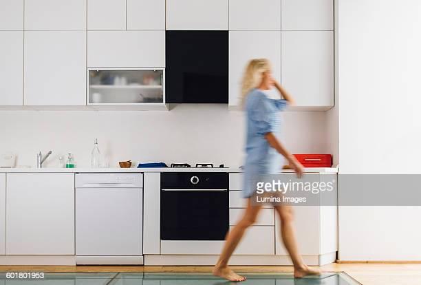 woman walking in modern kitchen - donne bionde scalze foto e immagini stock