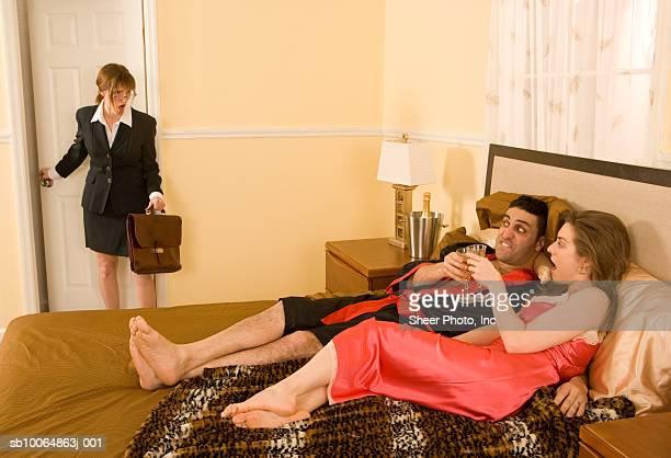 Woman walking in on couple in bedroom