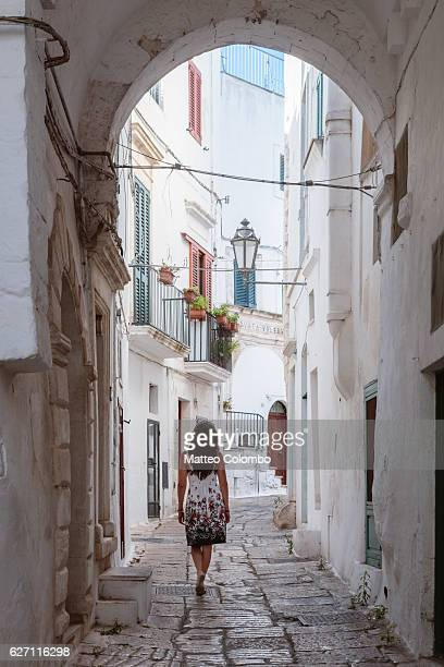 woman walking in ostuni (the white town), apulia, italy - ostuni stock photos and pictures