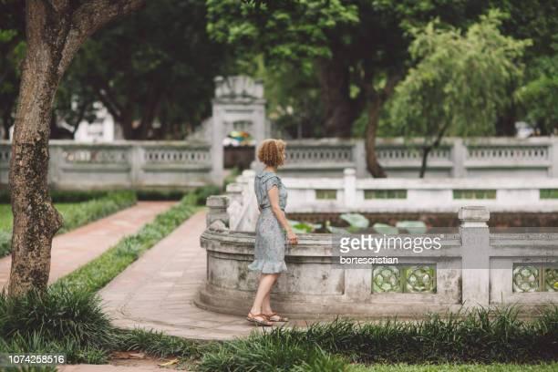 woman walking in park - bortes fotografías e imágenes de stock