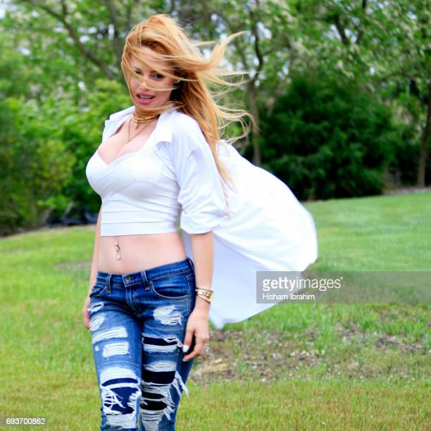 woman walking in park wearing open button down shirt, wind blowing in hair. - belly ring stock photos and pictures