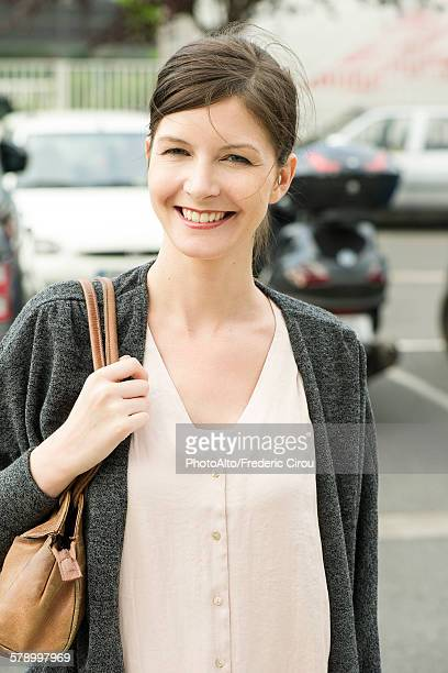Woman walking in parking lot, smiling cheerfully