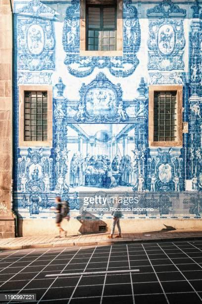 woman walking in porto against azulejos wall of the capela das almas church in porto - oporto portogallo foto e immagini stock