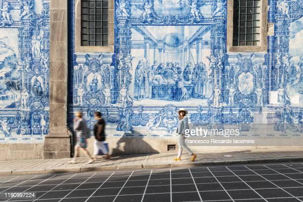 woman walking in porto against azulejos wall of the capela das almas church in porto - iacomino portugal foto e immagini stock