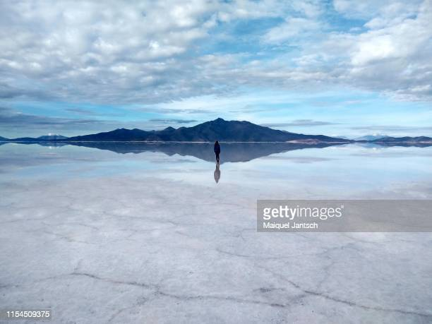 woman walking in salar de uyuni, bolivia. - reflection pool stock pictures, royalty-free photos & images