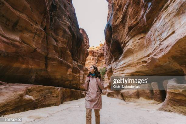 woman walking in siq canyon in petra - sandstone wall stock pictures, royalty-free photos & images