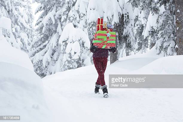 woman walking in snow carrying presents - peter snow stock pictures, royalty-free photos & images