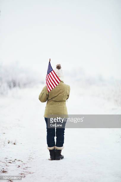 woman walking in snowy landscape with american flag - patriotic christmas stock pictures, royalty-free photos & images