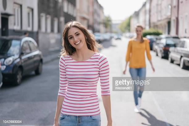 woman walking in street, followed by friend - following stock pictures, royalty-free photos & images