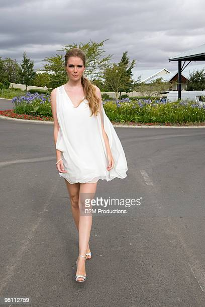woman walking in street - mini dress stock pictures, royalty-free photos & images