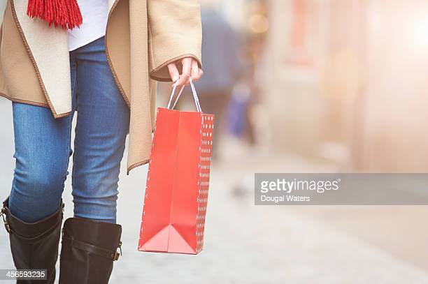 woman walking in street with gift bag, close up. - shopping bag stock pictures, royalty-free photos & images